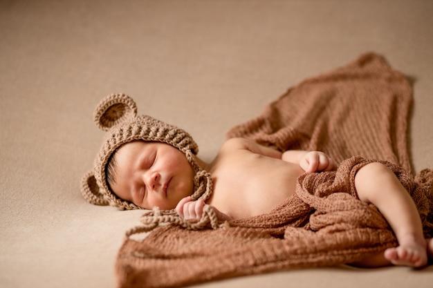 Новорожденный спящий ребенок в вязаной шапке лежит на коричневой ткани