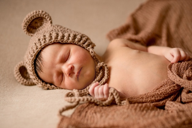 Новорожденный спящий ребенок в вязаной шапке лежит на коричневой ткани.