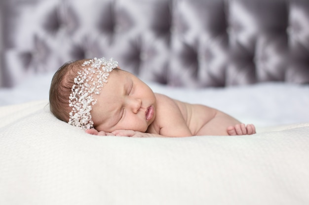 Newborn sleeping baby on stomach  on light background, close-up, lifestyle, the concept of purity and innocence, copyspace