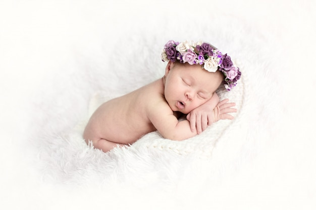 Newborn sleeping baby on stomach on  light background with wreath of purple flowers, close-up, lifestyle, the concept of purity and innocence