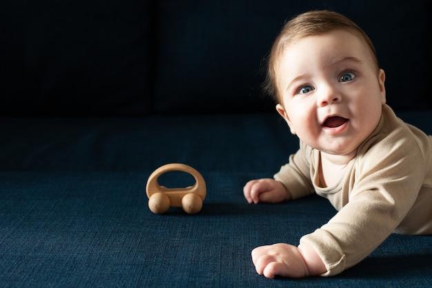 ベージュのボディースーツを着た新生児の男の子は、木のおもちゃの側面図で遊ぶ