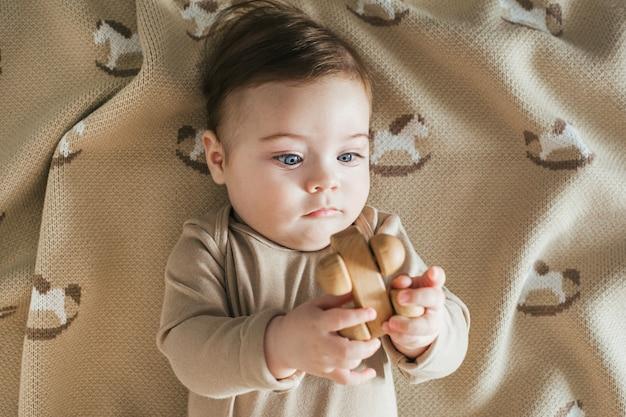 ベージュのボディースーツを着た新生児の男の子が木のおもちゃの上面図で遊ぶ