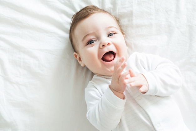Newborn toddler boy laughing on the bed