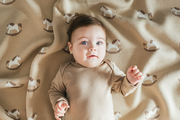 格子縞の上面図でカメラを見ているベージュのボディースーツの新生児の幼児の男の子の肖像画