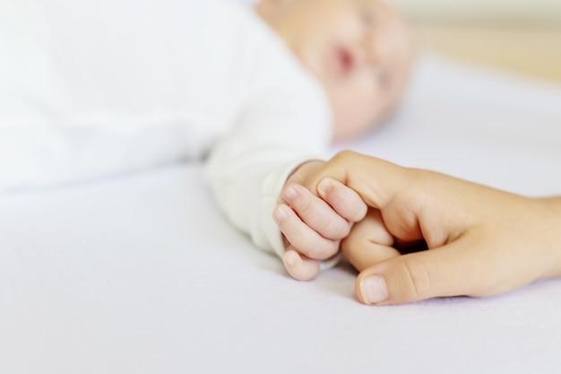 Новорожденный малыш держит сестру за руку