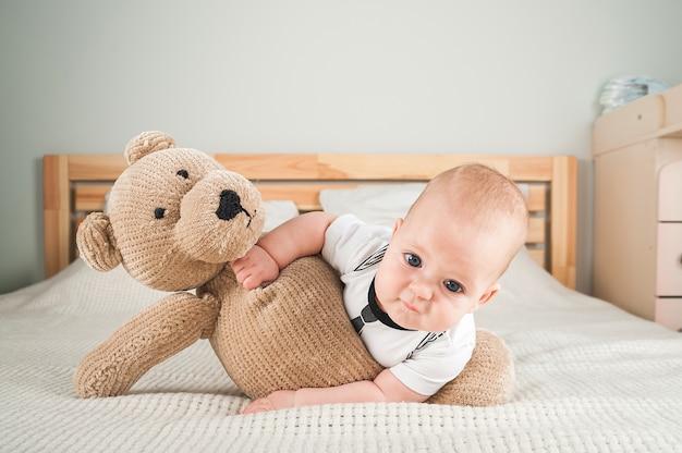 ベッドのクローズアップとコピースペースにおもちゃのクマと一緒に生まれたばかりの幼児。面白い赤ちゃんとぬいぐるみクマ