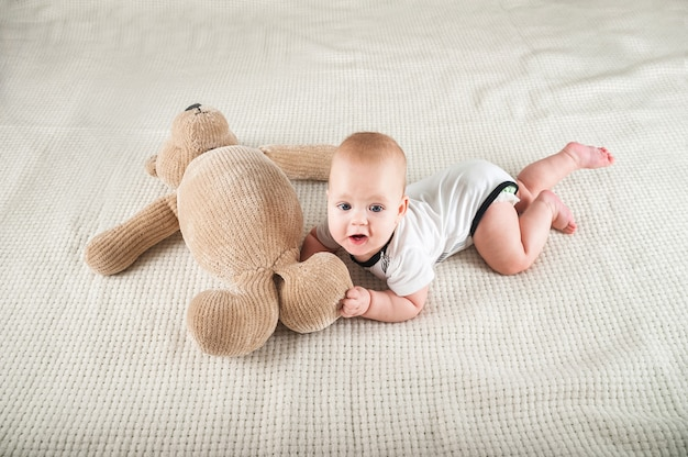 Newborn toddler with a toy bear on the bed close-up and copy space. funny baby and soft toy bear