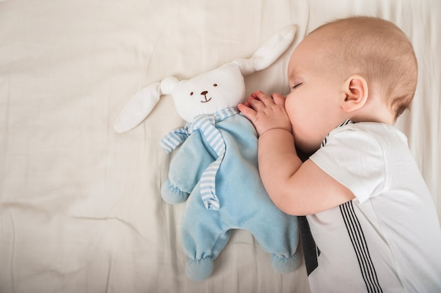 Newborn toddler with a toy on the bed close-up and copy space. the child sleeps on a large bed