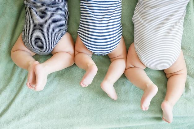 Новорожденные тройни лежат на животе на одеяле
