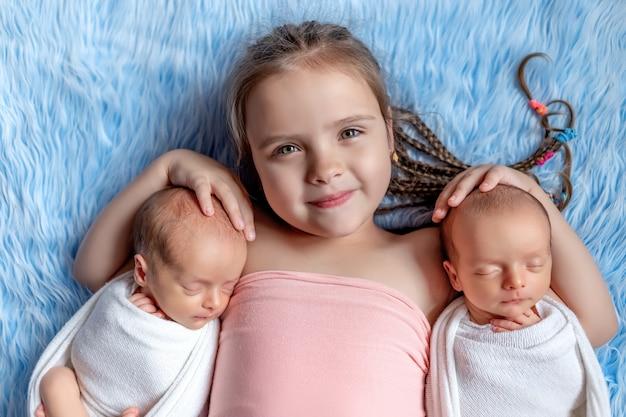 生まれたばかりの双子が青色の背景に妹と眠る