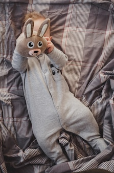 Newborn up to four months old lying on the bed with a toy hare
