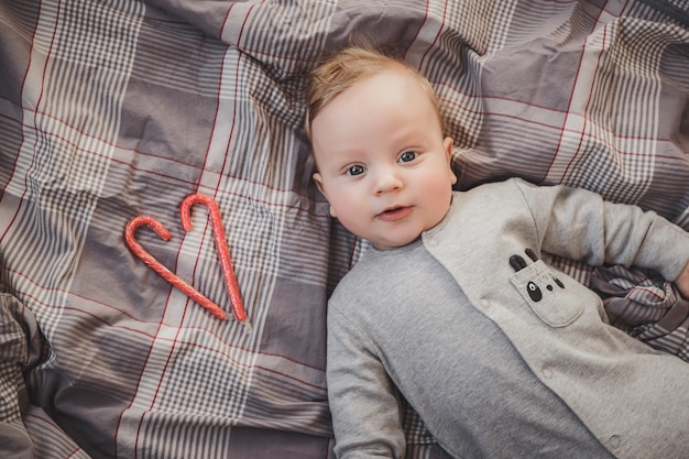 Newborn up to four months old lying on a gray bed, next to a red heart