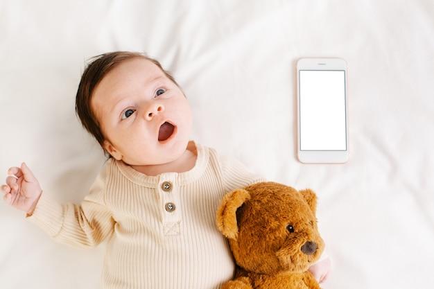 白いベッドと白い画面の携帯電話にクマと新生児