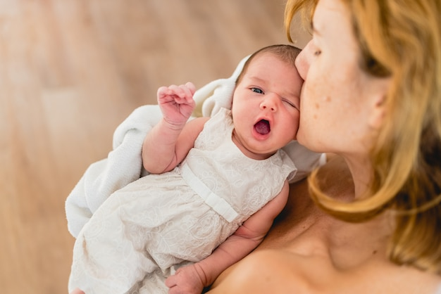 Newborn yawning in her mother's arms.