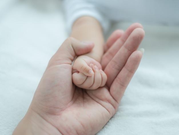Будьте отцом держать newborn концепцию предохранения от руки, счастливой семьи и младенца. мама и папа держат руку своего ребенка.