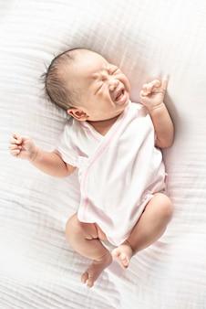 Лежать милого маленького младенца newborn плача на кровати.