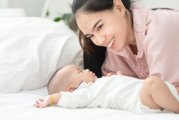 Закройте вверх по красивой молодой азиатской матери целуя newborn младенца на кровати. здравоохранение и медицина. азиатская девушка любит образ жизни.