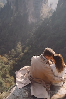 Newly enageged couple hugging and holding hands as they are sitting on a rock at zhangjiajie national forest park