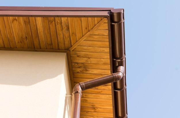 Новый водосточный желоб и водосточная труба на деревянном карнизе строящегося дома новой постройки.