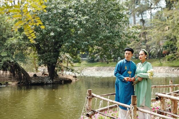 전통 의상을 입은 새로 결혼한 아시아 부부는 도시 공원의 연못에 서서 물을 바라보고 있습니다.