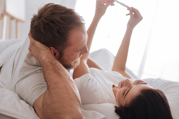 妊娠検査で陽性を示し、朝に一緒に将来の赤ちゃんを想像する新婚夫婦 Premium写真