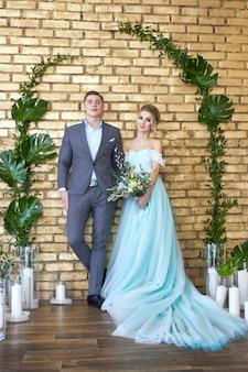 신혼 부부, 결혼식 전에 부부 사랑. 서로 사랑하는 남자와 여자. 청록색 드레스의 신부와 파란 양복에 신랑. 웨딩 장식, 웨딩 포토존