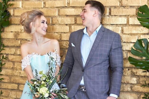 新婚夫婦、結婚式前の愛情のあるカップル。男と女はお互いを愛しています。ターコイズブルーのドレスを着た花嫁と青いスーツを着た新郎。結婚式の装飾、結婚式の写真ゾーン