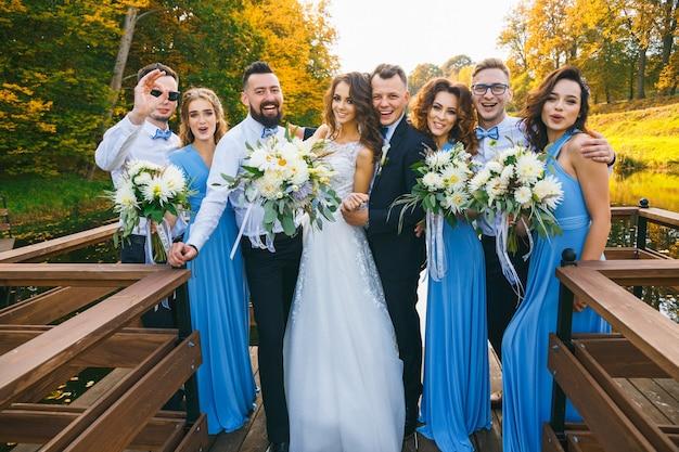 Молодожены с женихами и подружками невесты позируют на свадебной церемонии
