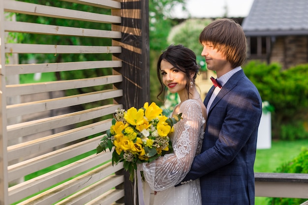 Newly married posing near by luxurious wooden mansion on wedding ceremony