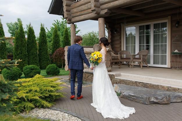 結婚式で豪華な木造の邸宅に入る準備ができて新婚