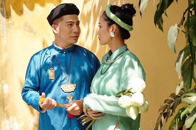 서로를 바라보는 전통 의상을 입은 새로 결혼한 베트남 남녀