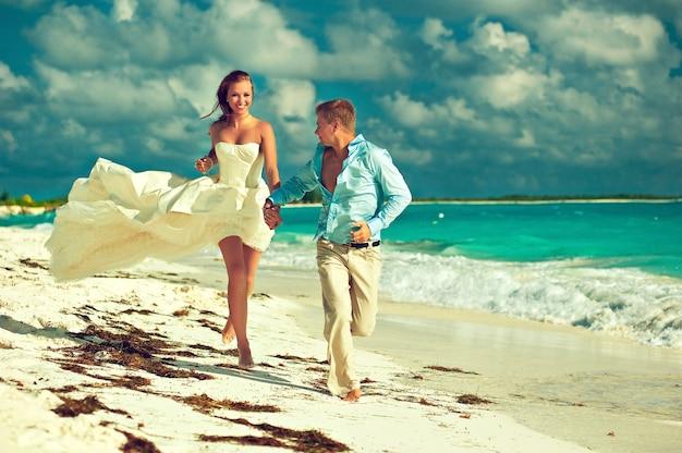 새로 결혼 한 젊은 아름다운 신부와 잘 생긴 신랑은 카리브해 열대 해변에서 해안선 결혼식을 따라 달리고 있습니다. 젊은 얼굴에 사랑과 행복