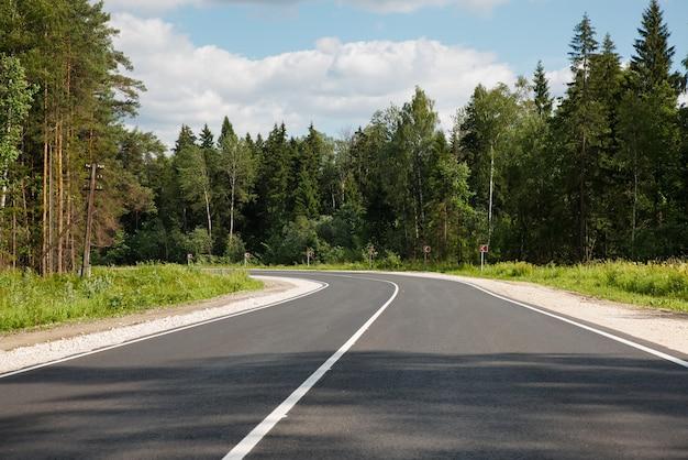 숲을 통과하는 새로 포장 된 도로