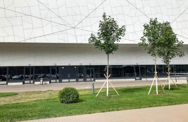 지원을 위한 말뚝이 있는 쇼핑 센터 근처에 새로 심은 나무와 덤불