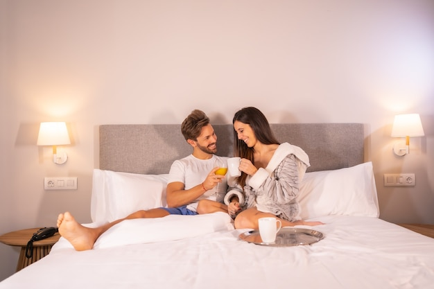 A newly woken couple in pajamas having coffee and orange juice for breakfast in the hotel bed in the morning, lifestyle of a couple in love.