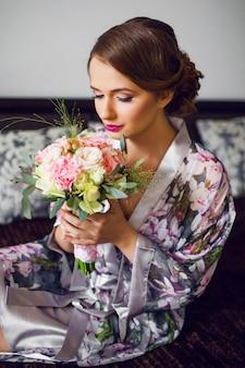 新婚の美しい女性が花のバスローブで結婚式の日の準備を開始します。