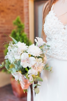 Newlywed bride holding white flower bouquet