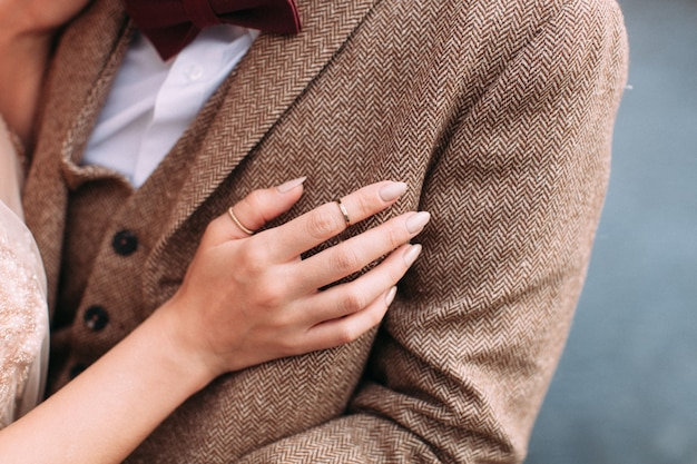 Newlywed bride put her hand with golden rings on her groom's chest in tweed jacket. concept of family, love, wedding day