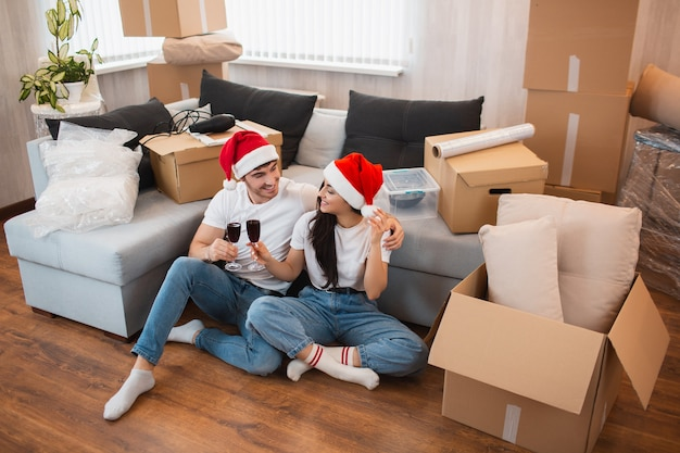 Молодожены встречают рождество или новый год в своей новой квартире. молодой счастливый мужчина и женщина пьют вино, празднуют переезд в новый дом и сидя среди коробок.