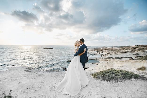 キプロスの海岸で白い岩の上を一緒に抱いて新婚者のカップル。背景の美しい風景でポーズをとってスーツで新郎新婦のウェディングドレス
