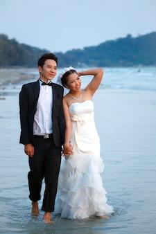 Newlywed couples walking beach