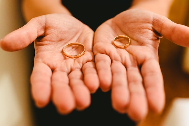 Newlywed rings shown in the hands of the bride and groom.