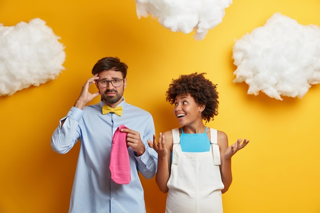 新婚の配偶者夫婦は、出産の準備をし、幼児服を購入し、困惑して黄色に躊躇します。家に両親を期待しています。家族と妊娠の概念。