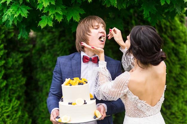신혼 부부와 신부 들러리가 결혼식 피로연에서 신선한 공기를 마시 며 함께 웨딩 케익을 먹으며 즐거운 시간을 보냅니다.