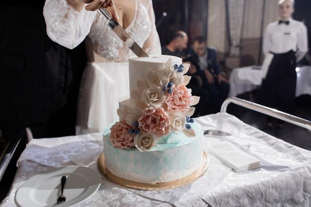 新婚夫婦はウェディングケーキを切っています。 無料写真
