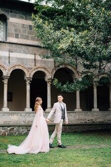 신혼 부부는 녹색 정원에서 걷고 손을 잡고있다