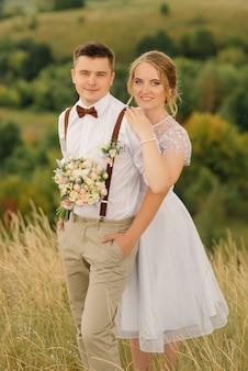 自然の美しい風景の中で新婚夫婦がポーズをとっている