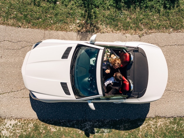 Newlyweds are riding in a beautiful white convertible on the road
