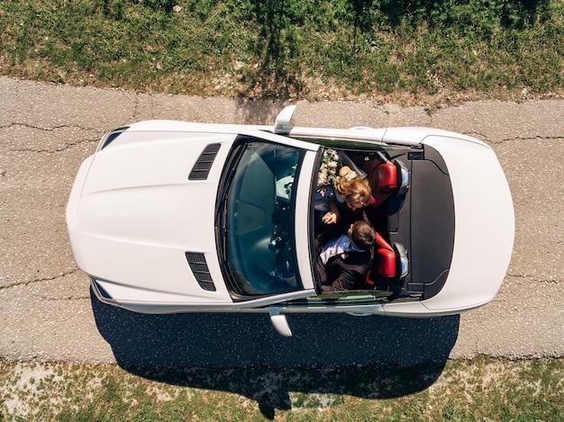 新婚夫婦は道路上の美しい白いコンバーチブルに乗っています