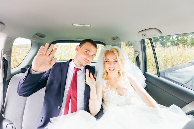 Newlyweds are sitting in the back seat of a chic car looking at the camera and waving their hands